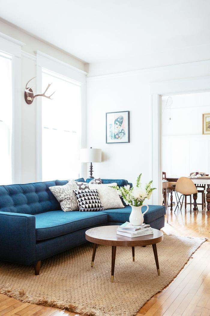 salon aux tons neutres et aux accents de déco scandinaves sublimé par un canapé bleu paon
