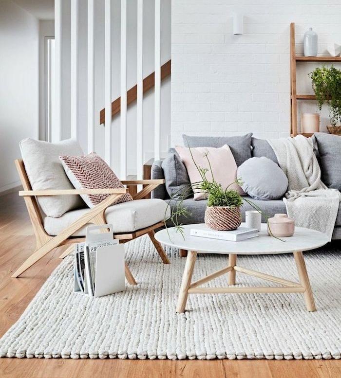 deco scandinave salon, canapé gris avec coussins décoratifs, chaise en bois avec housses blanches, murs blancs