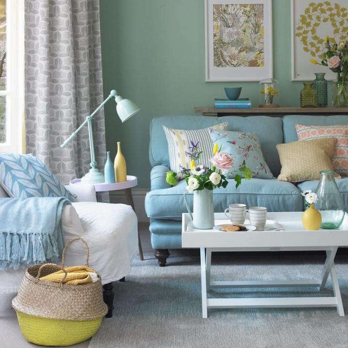 mur couleur vert pastel, canapé shabby chic, coussins multicolores, table basse blanche, fauteuil revêtu en blanc, panuer de rangement, deco florale