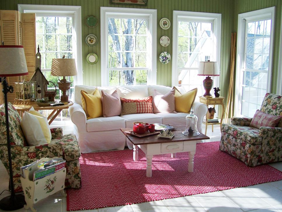 salon shabby chic, canapé blanc, tapis rouge et fauteuils à motifs floraux, lambris vert et decoration de vaisselle dessus, coussins decoratifs multicolores, table basse vintage
