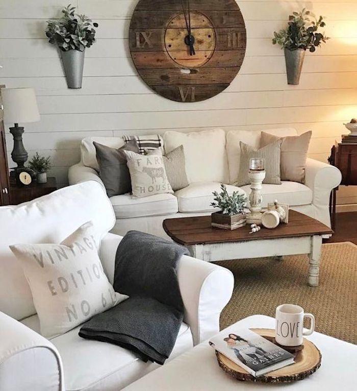 lambris blanc, canap;e shabby chic blanc, fauteuil blanc, table basse en bois, coussins motifs vintage, horloge vintage en bois, bouquets de fleurs