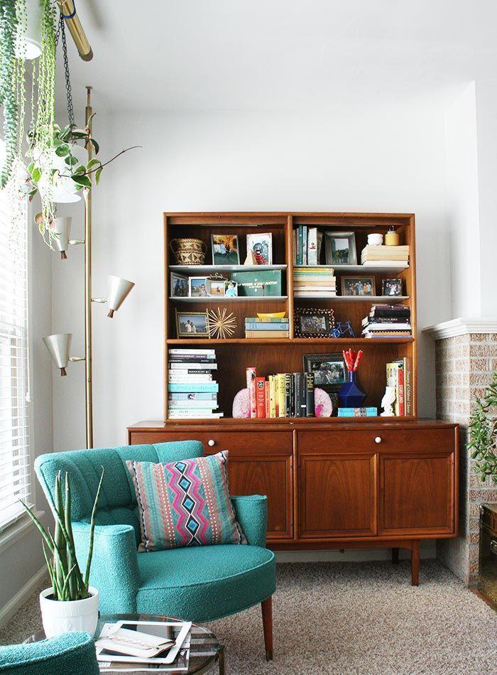 un coin de lecture de style vintage avec canapé bleu sarcelle des années 50s et une crédence d'aspect rétro