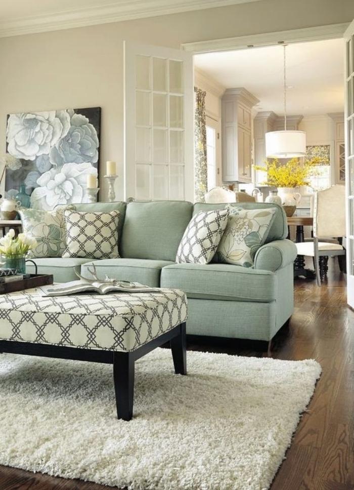 modele de salon vert d eau, avec canapé vert, tapis blanc, table marron avec coussin blanc à motifs géométriques, parquet marron, panneau decoratif à motifs de fleurs
