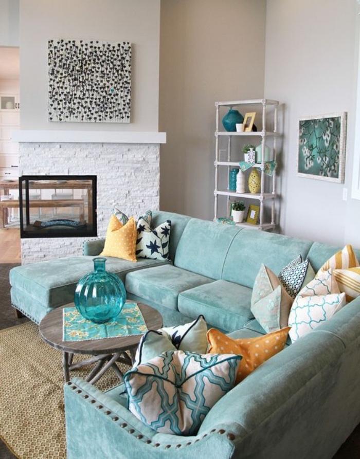 idée de canapé coueleur vert d eau dans in salon moderne bord de mer, table basse en bois ronde, tapis beige, cheminée en pierre, couleur gris perle, coussins bleu, blanc et jaune