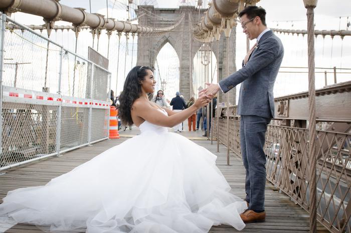 photo de couple originale sur un pont, la mariée se met à genoux