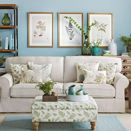 canapé shabby chic blanc cassé, tapis et mur couleur bleue, coussins et table basse tapisserie motifs floraux, étagère en bois et métal