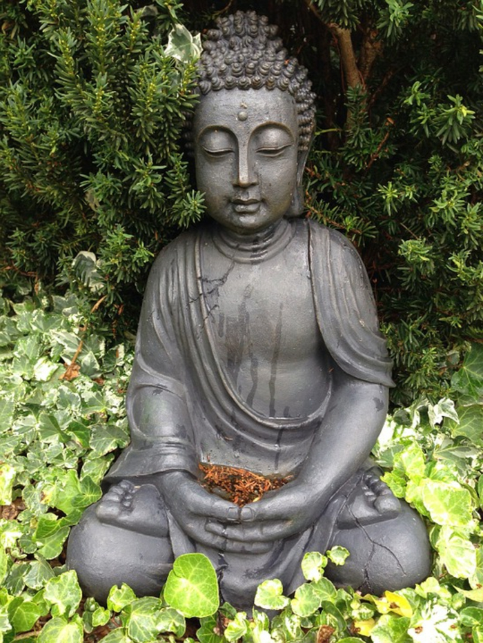 statuette de bouddha, élément essentiel de la déco de jardin zen, végétation verte exubérante, paysage oriental