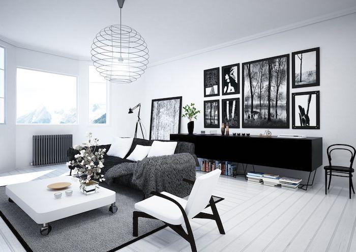 salon mur blanc, parquet en bois peint en blanc, armoire noir, cadres photo noirs, canapé noir avec coussins blancs