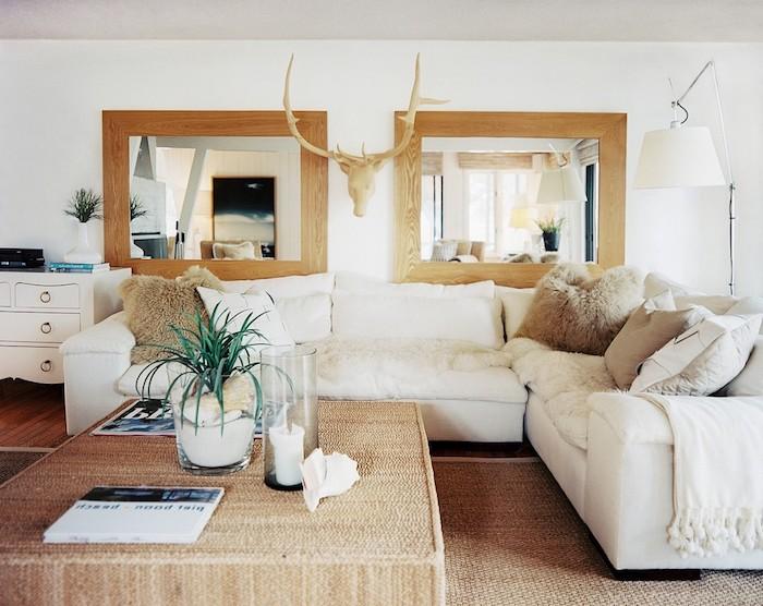 esprit scandinave, grand miroir en cadre de bois, cornes de cerf en bois, canapé d'angle blanc avec coussins décoratifs