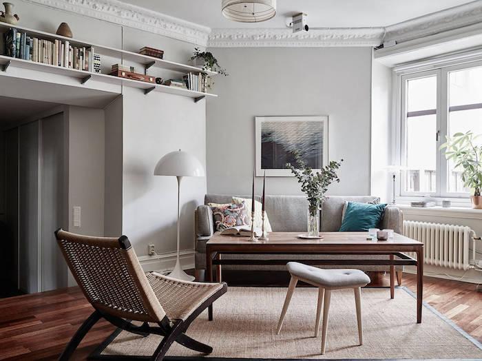 ambiance scandinave, plafond blanc avec déco en plâtre, étagère murale en bois peinte en blanc, canapé gris