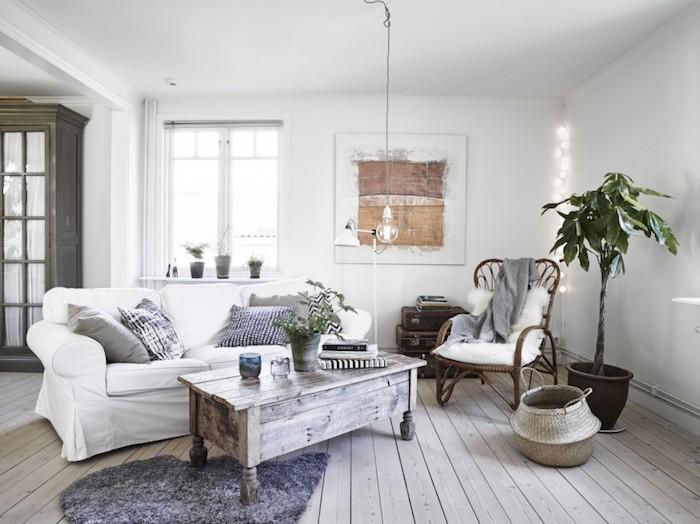 salon mur blanc, tapis en faux fur gris, panier en fibres végétales, plante, coussins décoratifs en gris