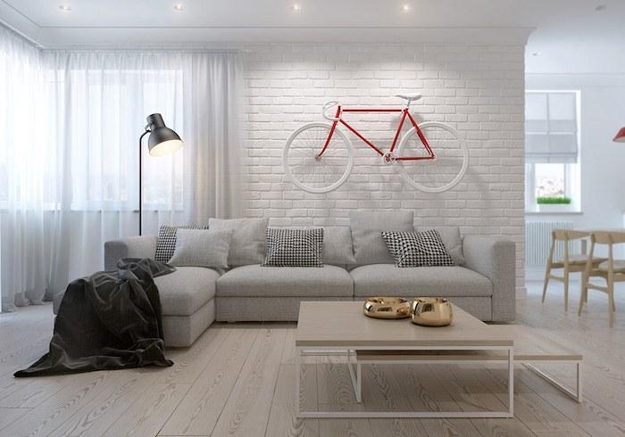 salon mur blanc, parquet de bois claire, canapé en tissu gris avec coussins décoratifs, lampe sur pied noire