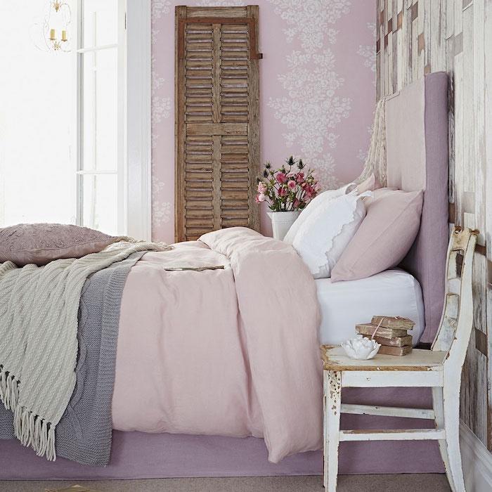 style shabby chic comment faire, chambre a coucher, mur rose a motifs fleurs blanches, porte en bois, lit mauve et linge de lit rose blanc et gris, chaise usée en guise de table de nuit