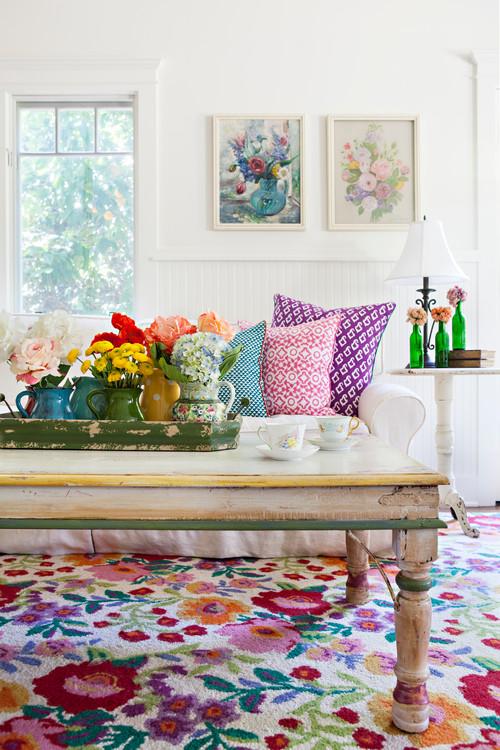 canapé shabby chic blanc, tapis et coussins multicolores motifs imprimés floraux, table en bois brut, decoration de fleurs, mur couleur blanche, peintures de fleurs