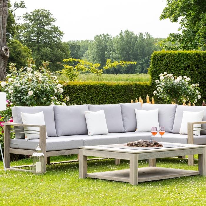 salon de jardin en bois sur une gazon vert, séparation naturelle de buis vert, rosiers, lanterne avec bougie