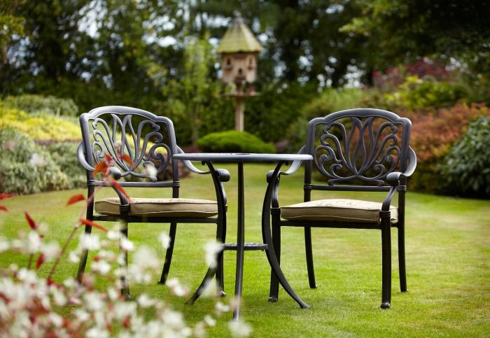salon de jardin simple sur un gazon, table ronde noire er chaises noires avec des coussins d assise beige, plusieurs arbustes et arbres en bordure