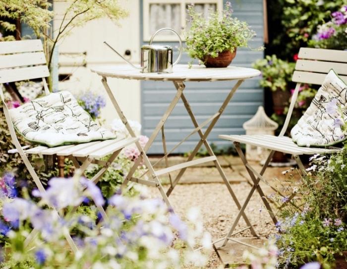 idee amenagement petit jardin, salon de kardin en table et chaise en metal, gravier dans un cadre naturel, parterres de fleurs
