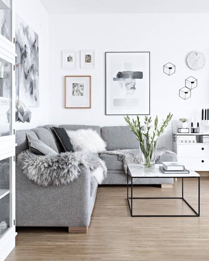 appartement scandinave, murs peints en blanc, canapé d'angle en gris, table en marbre et fer forgé, vase en verre avec fleurs blanches