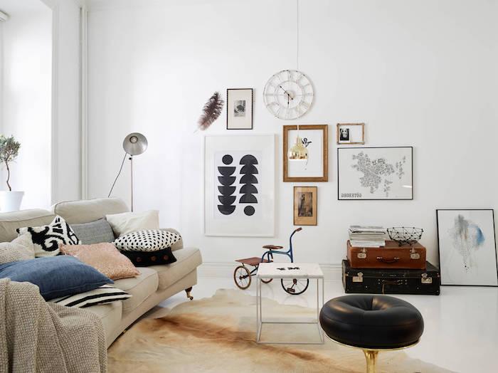 intérieur scandinave, tabouret en pied doré avec siège en cuir noir, petite table blanche, cadres photo en bois