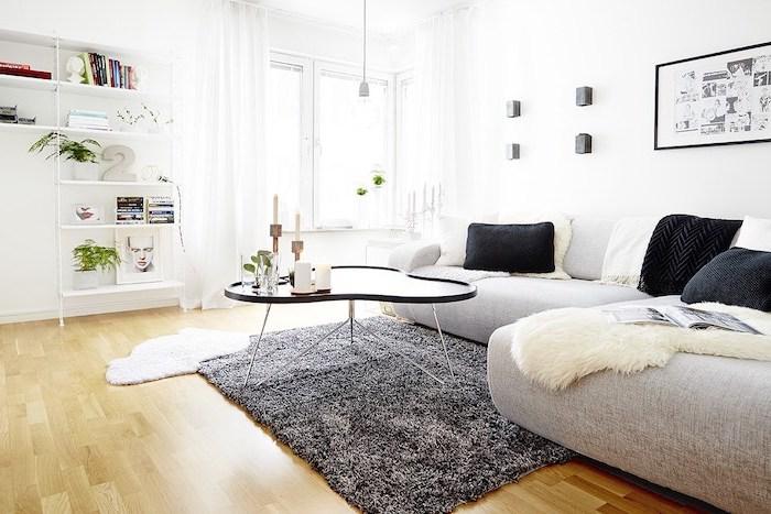 tapis scandinave, étagères en bois peintes en blanc, table asymétrique noire, coussins noirs