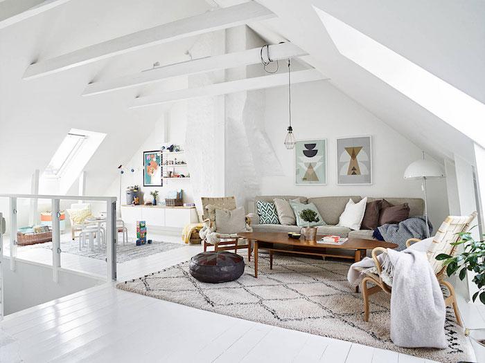 salon mur blanc, parquet en bois peint en blanc, canapé beige avec coussins, table en bois, pouf en cuir noir, plantes vertes