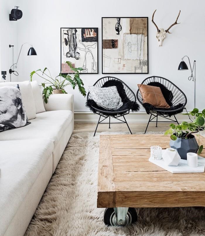 tapis scandinave, canapé blanc en cuir, chaise noire avec coussins décoratifs, art prints avec cadres noirs