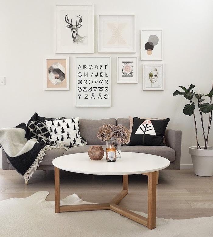 meuble scandinave, canapé beige avec coussins décoratifs, table basse ronde avec pieds en bois, cadres photos avec art prints