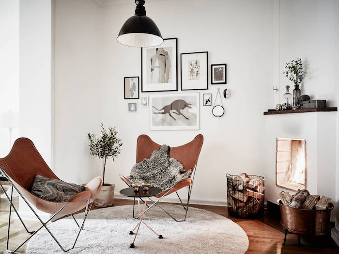 intérieur scandinave, lampe suspendue noire, mur de cadres art prints, tapis rond blanc, chaise papillon marron