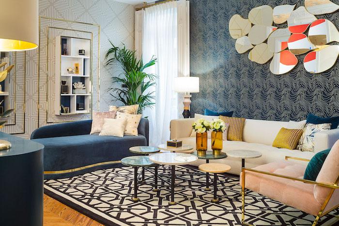 papier peint motifs géométriques, canapé en velours bleu, fauteuil en laiton avec housse en rose pastel, vase en verre jaune
