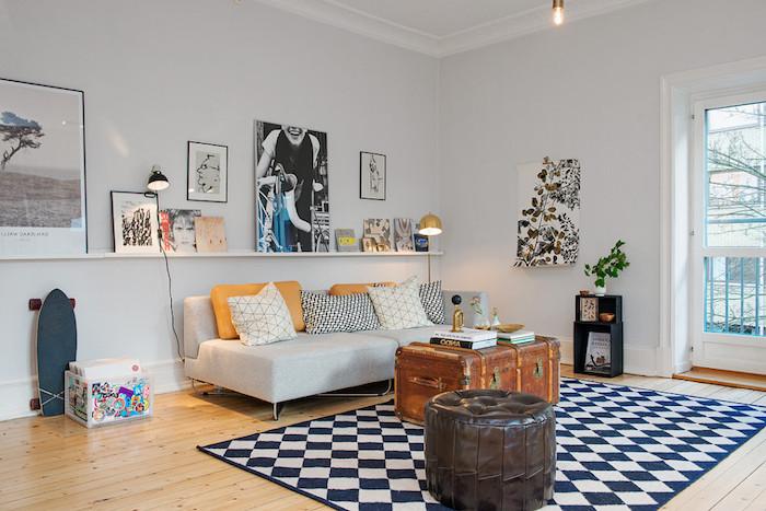 salon mur blanc, cadres photo noirs, canapé bas gris avec coussins jaune moutarde, coffre en bois, porte vers le balcon