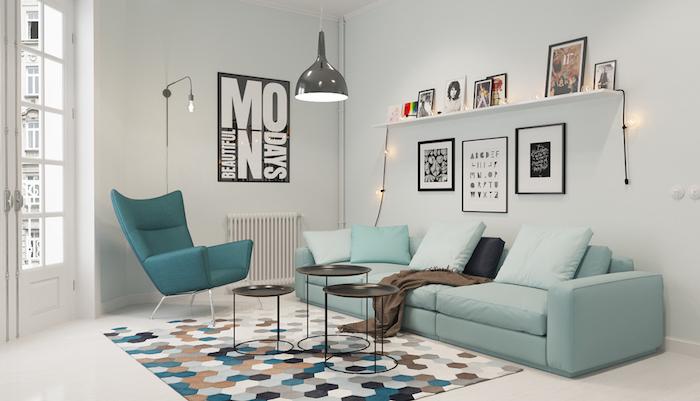 intérieur scandinave, murs peints en blanc, étagère en bois, cadres photo noir, canapé en bleu pastel