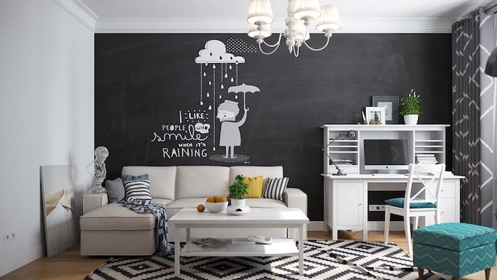 appartement scandinave, parquet en bois, tapis en blanc et noir à motifs géométriques, pouf en bleu et vert, mur noir avec sticker décoratif