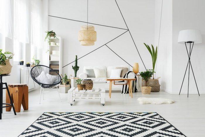 décoration scandinave, murs blancs avec lignes fines en noir, suspension luminaire en fibre végétale, plantes exotiques vertes