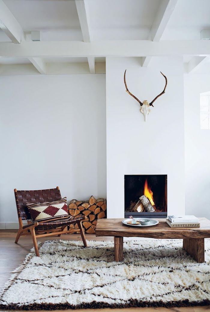 deco scandinave, cheminée blanche, cornes de cerf en bois, chaise en bois marron, table basse en bois, tapis blanc et marron