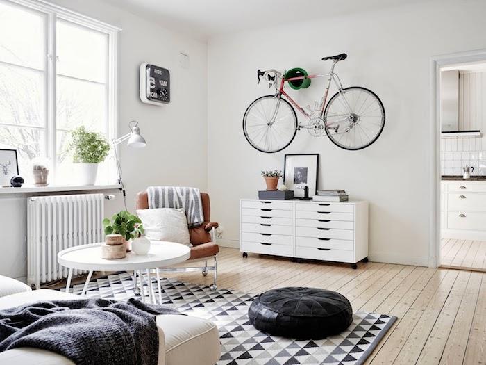 esprit scandinave, parquet en bois clair, pouf en cuir noir, canapé beige, table ronde en blanc, fauteuil en cuir marron