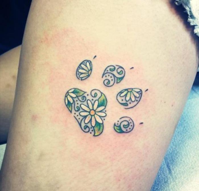 tatouage chat, marguerites et feuilles vertes dans les empreintes de pattes