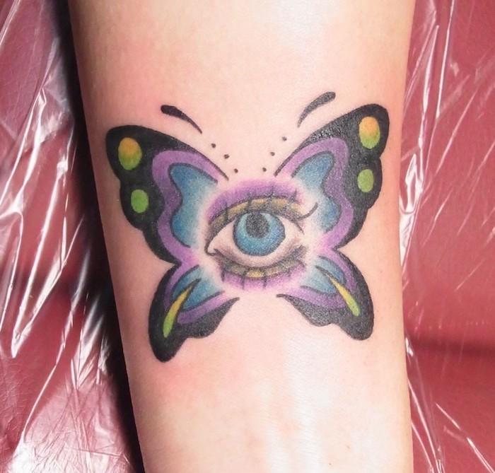 tatouage symbolique, dessin sur la peau, tatouage papillon multicolore avec yeux bleus