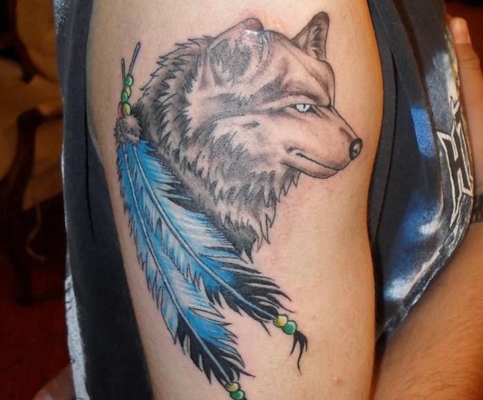 tatouage homme, dessin sur la peau avec loup et plumes bleues, tatouage sur l'épaule
