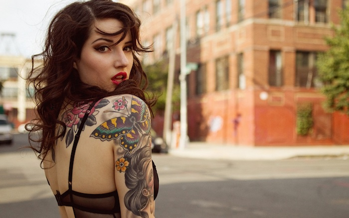 femme tatoué, coiffure avec boucles en marron foncé, maquillage avec rouge à lèvre, tatouage sur le bras