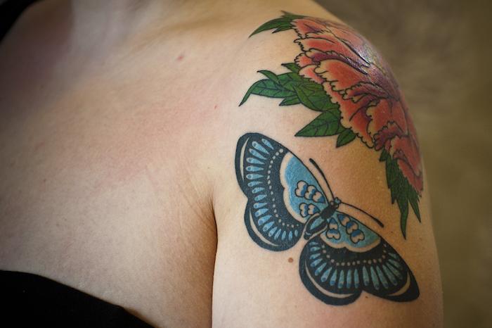 tatouage papillon, dessin en couleurs sur l'épaule, tatouage avec fleur rouge et papillon bleu
