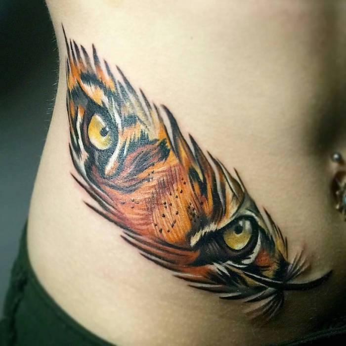 idée tatouage femme, dessin sur la peau à design plume et yeux de tigre, tatouage en couleurs