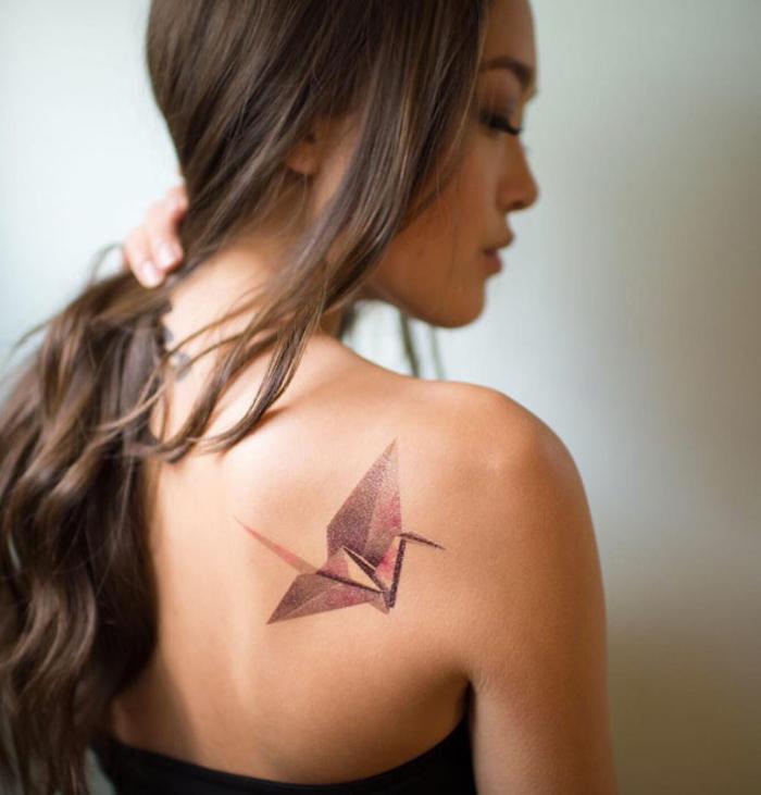 un tatouage géométrique rose et mauve en forme de grue inspiré par l'art de l'origami
