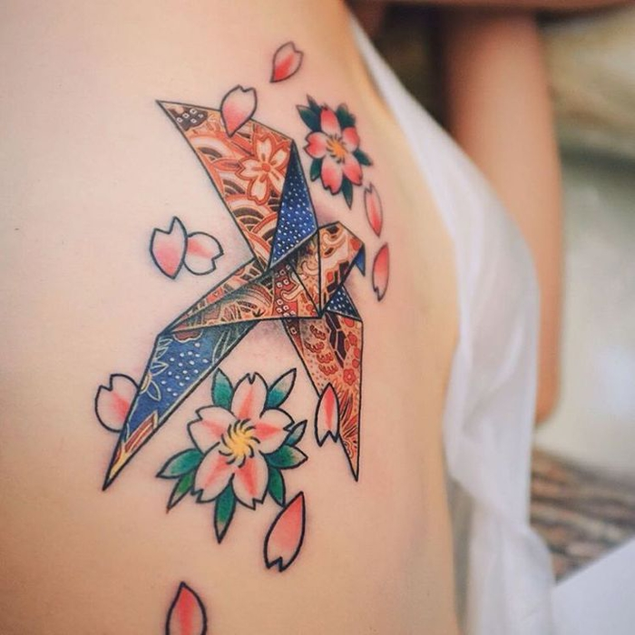 motif de tatouage japonaise représentant une colombe origami en couleur associée à de petites fleurs de cerisier