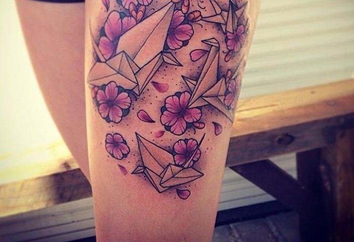 un tatouage géométrique représentant un grand dessin graphique et réaliste combinant le motif origami et floral