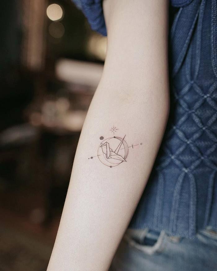 un tatouage minimaliste représentant une grue origami placée au centre d'une sphère armilaire