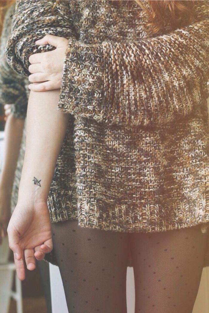 un tatouage minimaliste au poignet en forme de figure origami minuscule