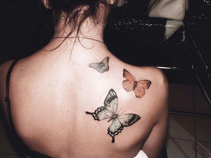 tatouage épaule femme, petits papillons en couleurs, femme aux cheveux attachés