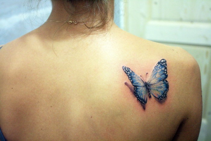 tatouage papillon 3d, collier en or, cheveux brun attachés, dessin papillon bleu