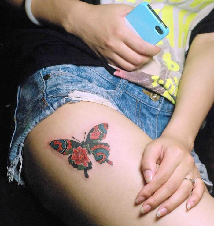 tatouage symbolique, paire de jeans en denim avec t-shirt noir, bague femme avec cristal, tatouage papillon en rouge et noir