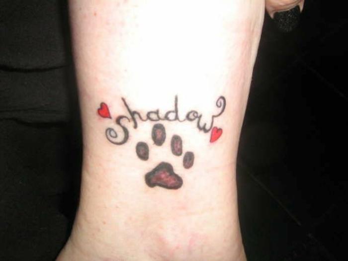 tatouage patte de chien, script tatoué et deux coeurs rouges, tatouage artistique